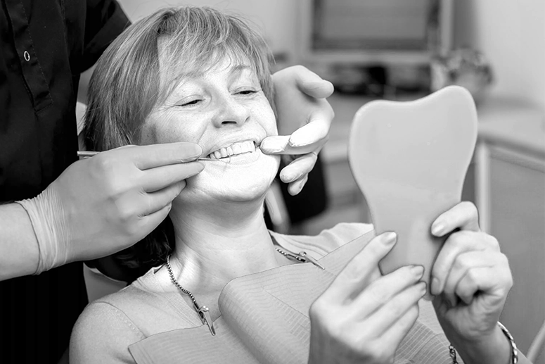 A black and white image of a patient sitting in a dental chair in a treatment room at Clinica Cloe