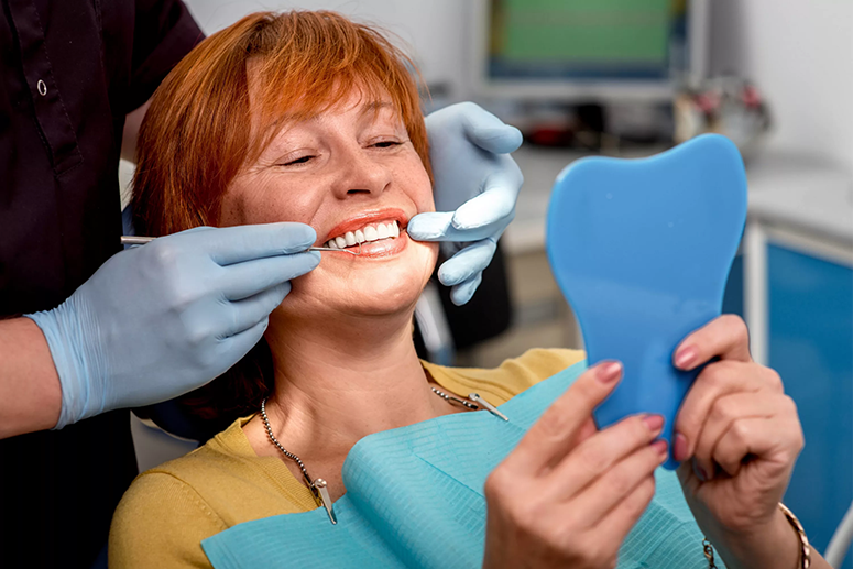 A color image of the same patient sitting in a dental chair in a treatment room at Clinica Cloe