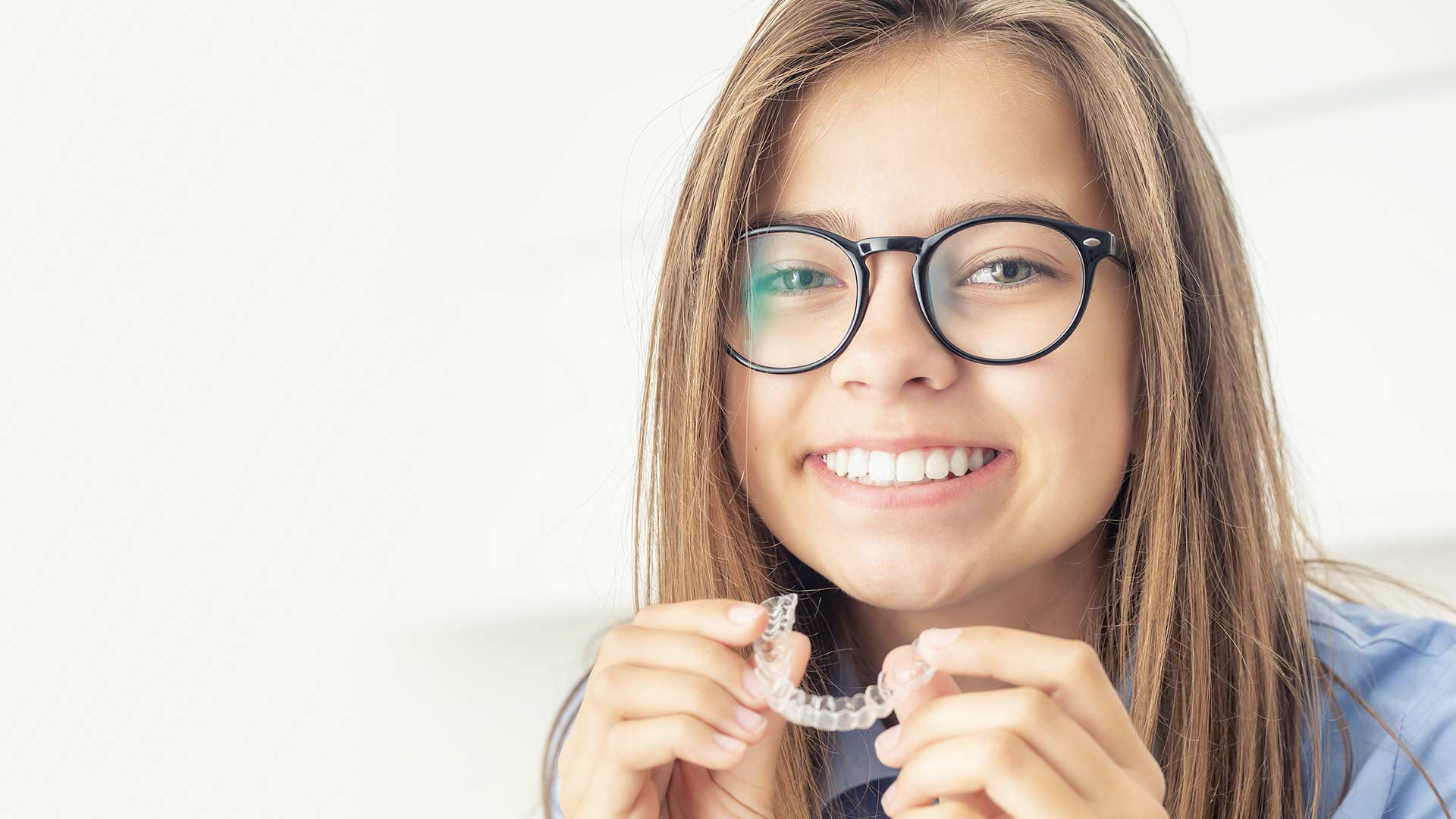 A teenage girl wearing glasses smiles to show her new straighter teeth while holding a clear aligner