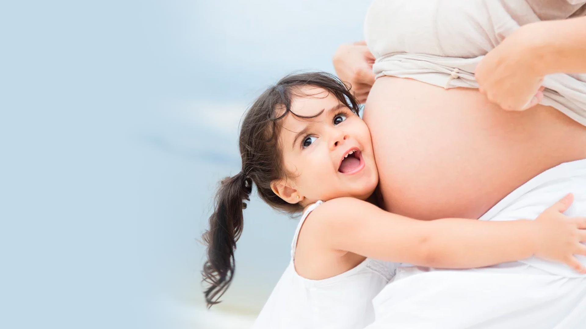 Una niña pequeña escuchando el vientre de su madre embarazada mientras le abraza