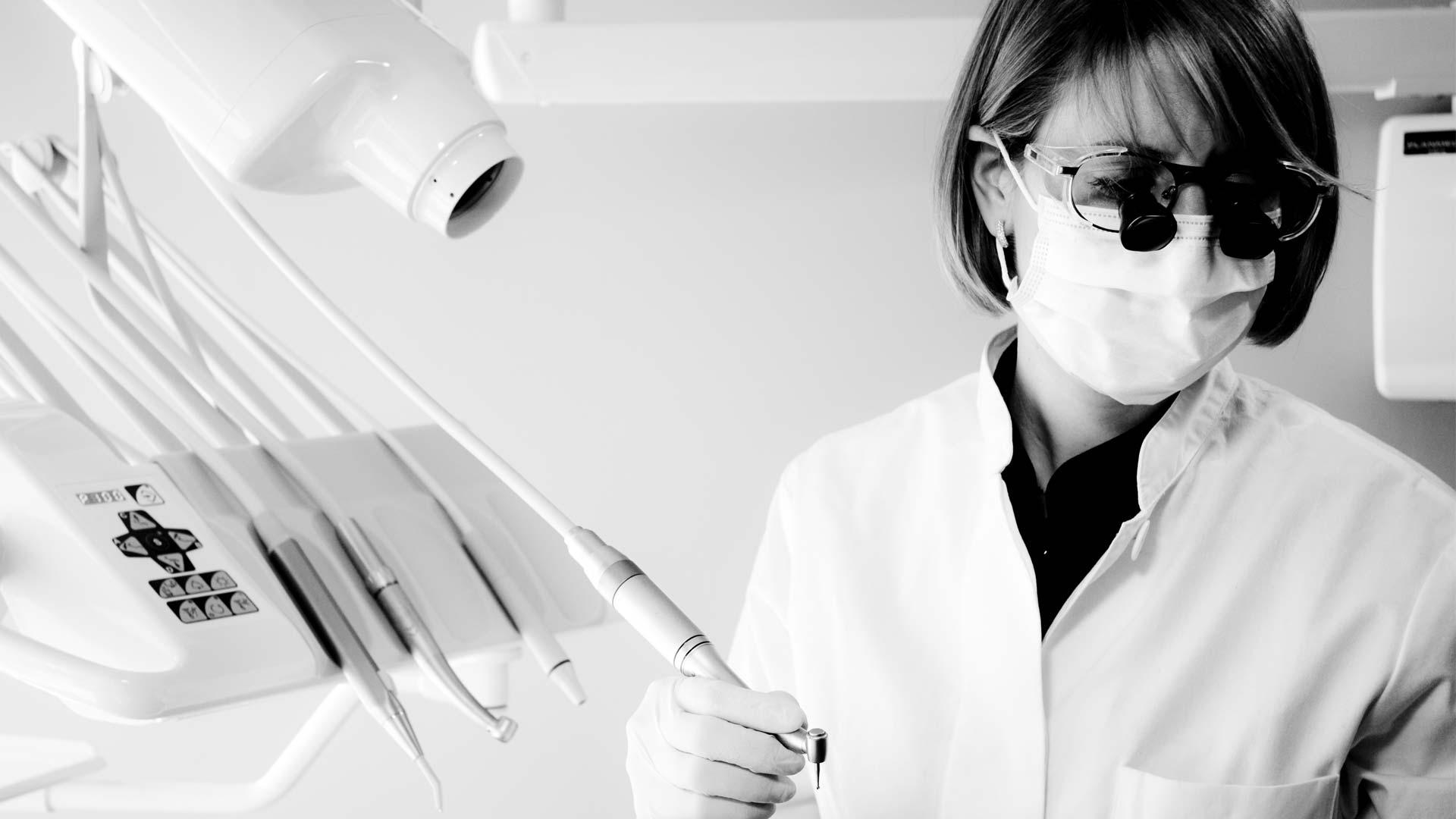 La Dra. Mya S. Choufani lleva una máscara quirúrgica y lupas dentales en Clínica Cloe en Madrid