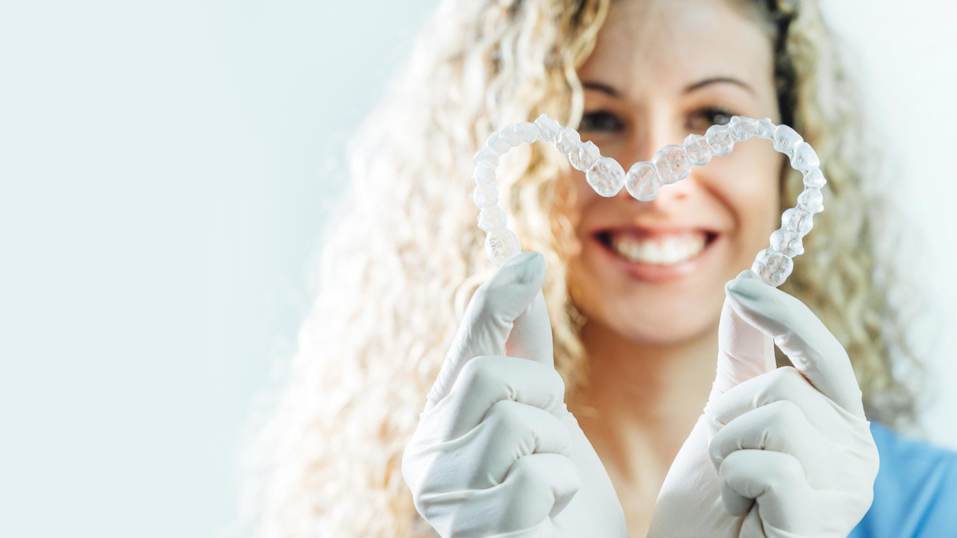 A dentist smiles and holds up two clear aligners in the shape of a heart.