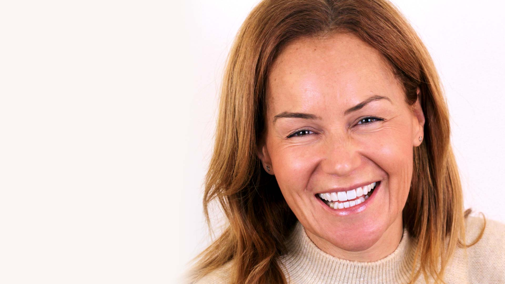 A woman smiles confidently after having Digital Smile Design dental treatment.